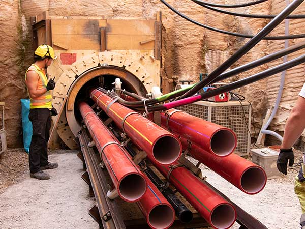 Da in der Baugrube der zur Verfügung stehende Platz begrenzt ist, erfolgt der Einzug des Rohrbündels in das Vortriebsrohr mit Hilfe eines Zugkopfes in mehreren Abschnitten auf Rollenringen, die mittels Zugstangen in 2 m Abstand.